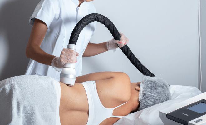 Na imagem: mulher deitada de lado enquanto uma aplicadora realiza uma sessão de Criofrequência corporal na lateral de sua barriga